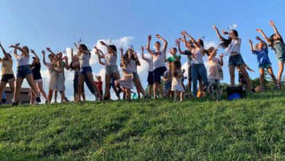 Campers dancing on a grassy hill.