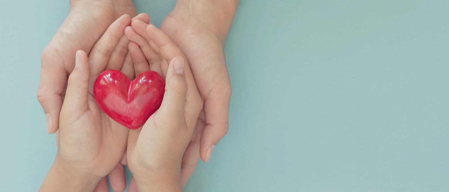 A pair of adult hands and child hands holding a red heart.