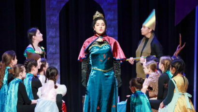 Anna singing in the performance of the musical Frozen.