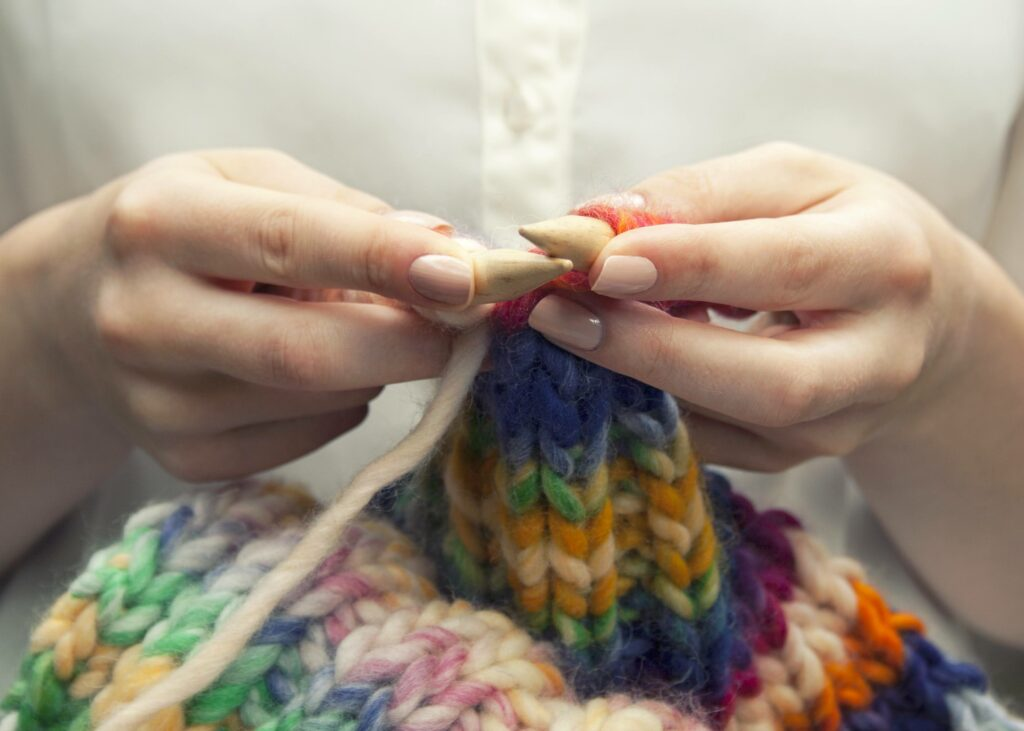 Young woman knitting a woolen colorful scarf. She is using bamboo knitting needles, size ten. Only her hands and arms are showing on the image. She has manicured nails. Neutral colored nailpolish. She is wearing an ivory colored blouse with transparant buttons. Rolled up sleeves, bare arms are visible. The knit has pastel colors as well as brighter colors. Pink, blue, green, orange, ecru and yellow.