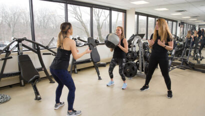 Women in a group exercise class with a trainer.