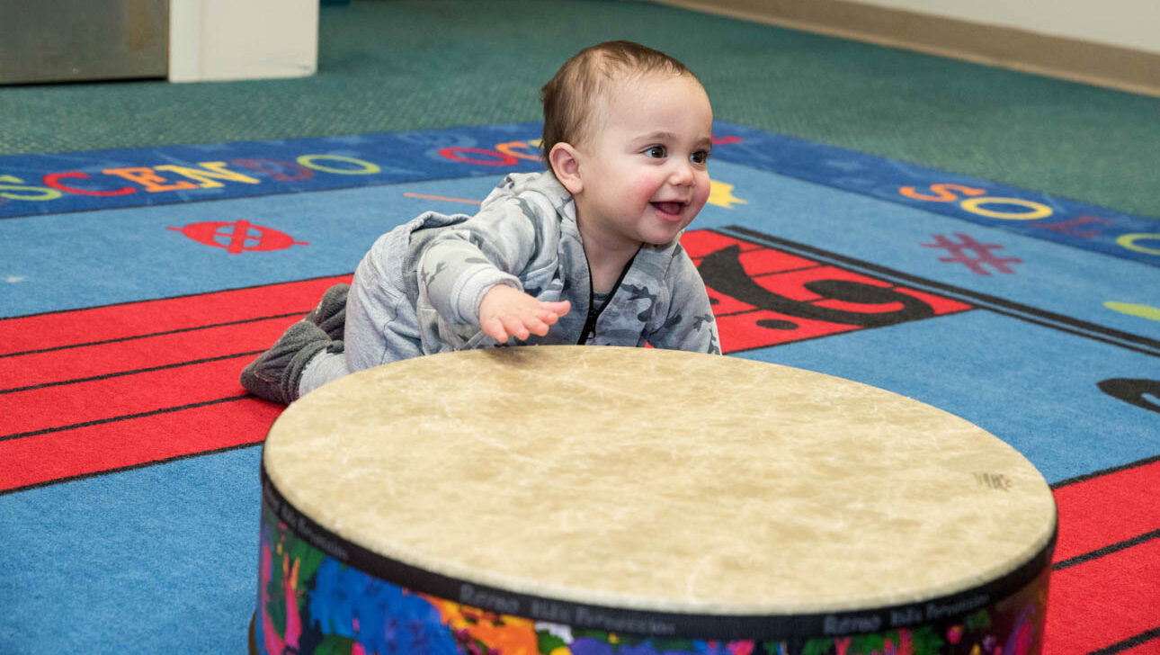 Baby crawling on a drum.