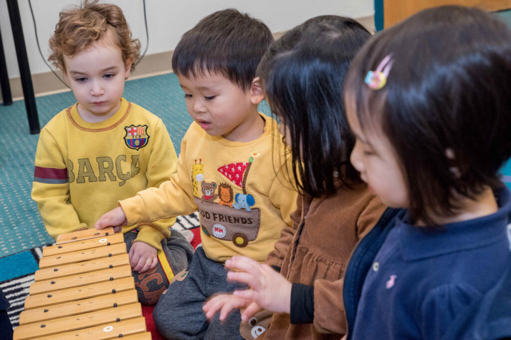 Group of toddlers playing with a xylophone.