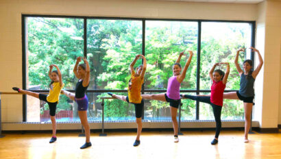 Line of girls using the barre for dance class.