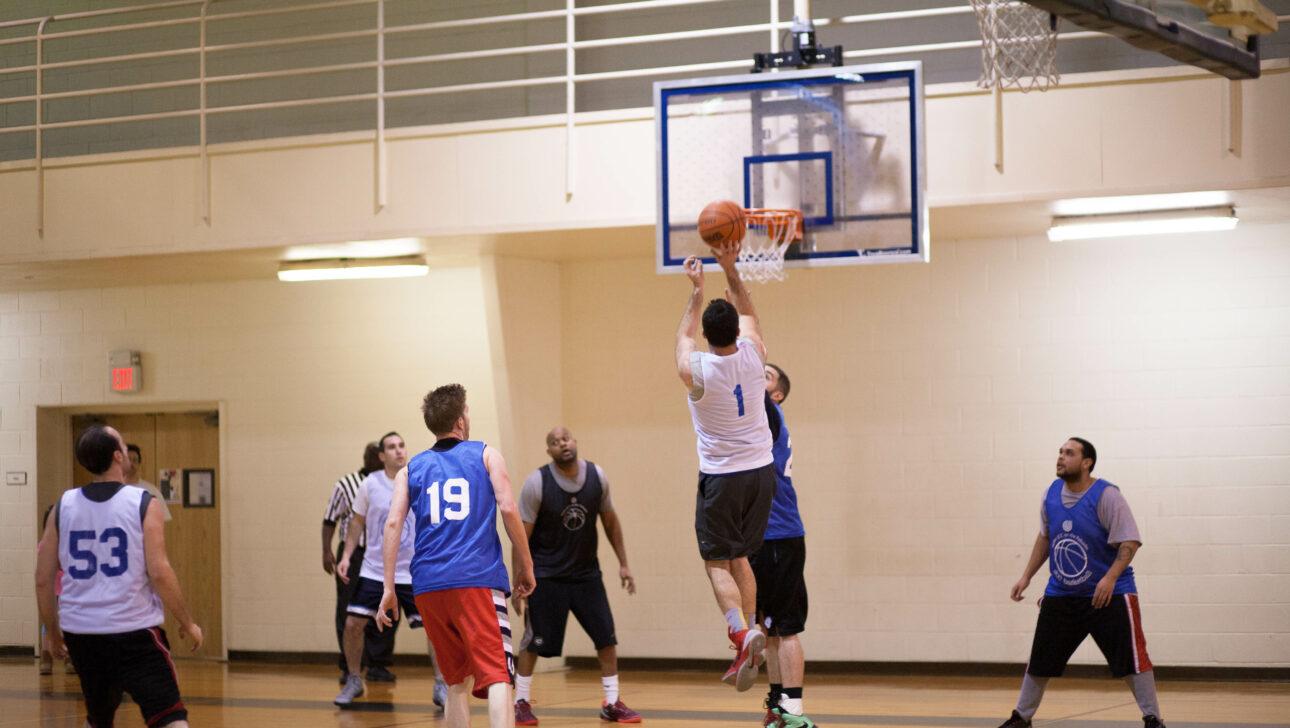 Men playing a basketball.