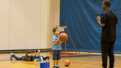 Young boy practicing shooting a basketball.