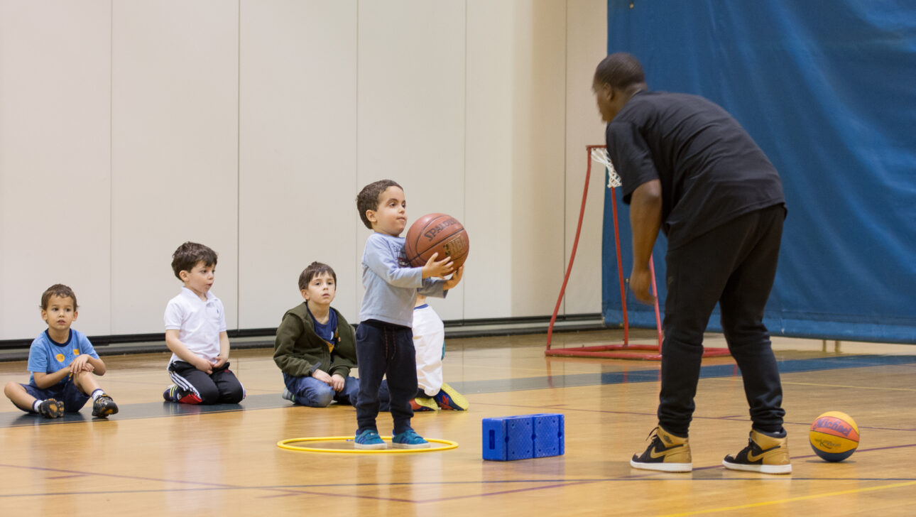 Young boy being coached in basketball.
