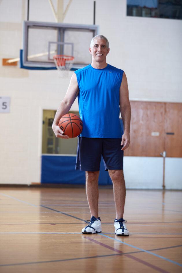 Man posing holding a basketball.