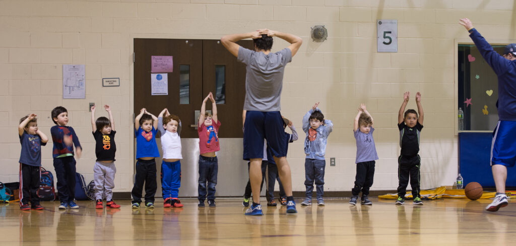Coach showing young boys how to stretch for basketball.