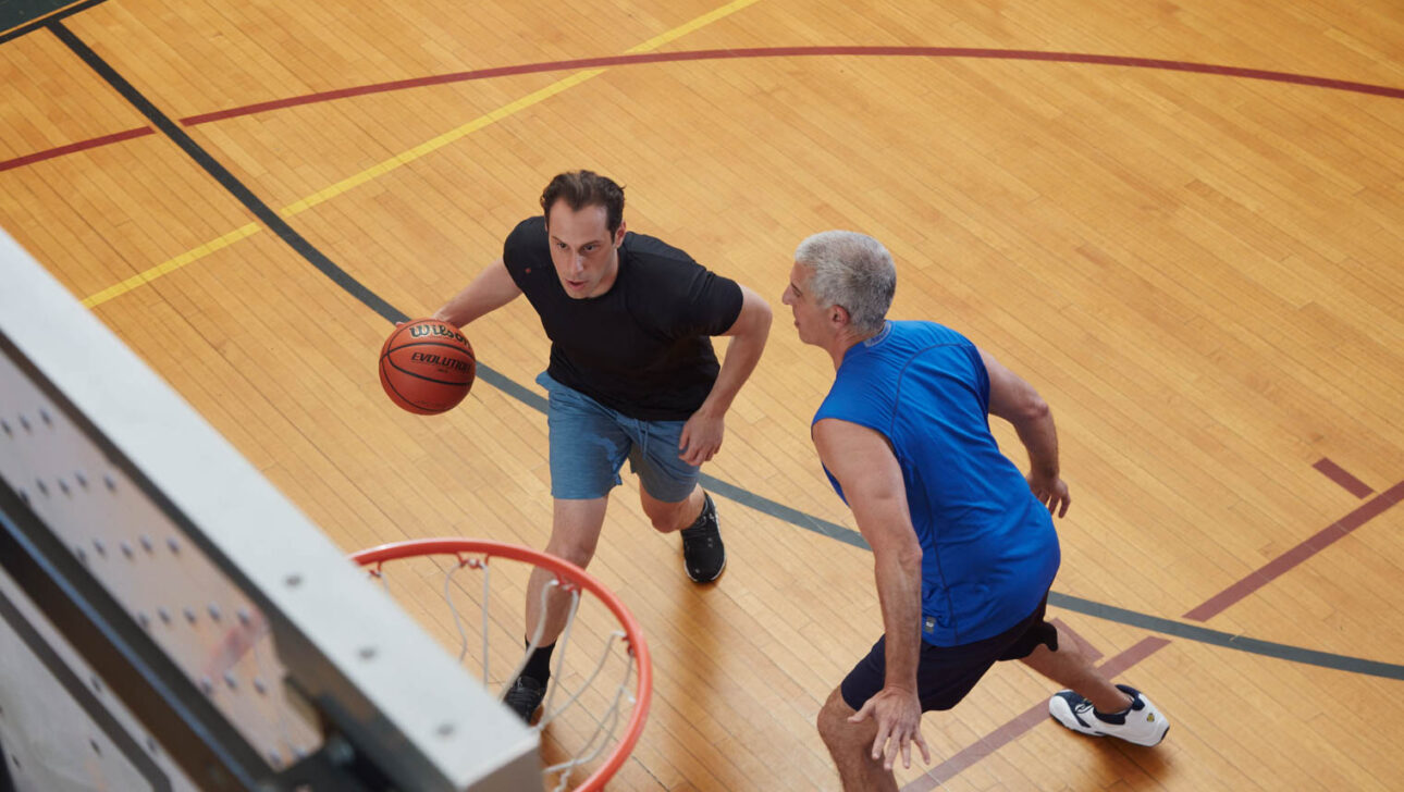 Two adult men playing basketball.