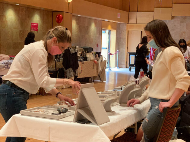 People looking at items at a boutique table.