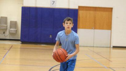 Boy shooting basketball.