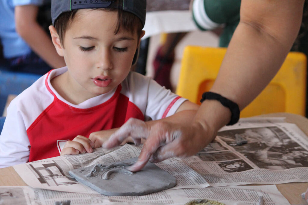 Boy created something out of clay with teachers help.
