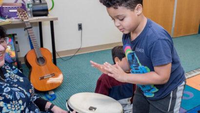 Young boy playing a bongo.