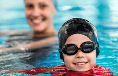 Instructor and student smiling in the pool.