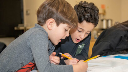 Two boys working on a worksheet together.