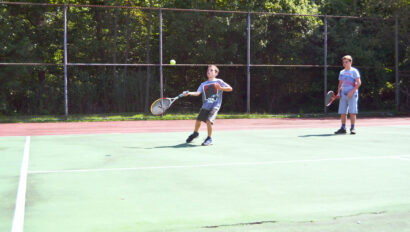 Boys playing doubles tennis.