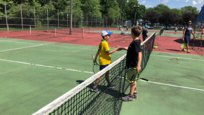 Boys shaking hands on the tennis court.