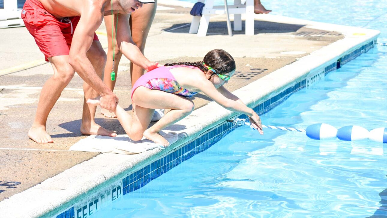 Child diving into a pool.