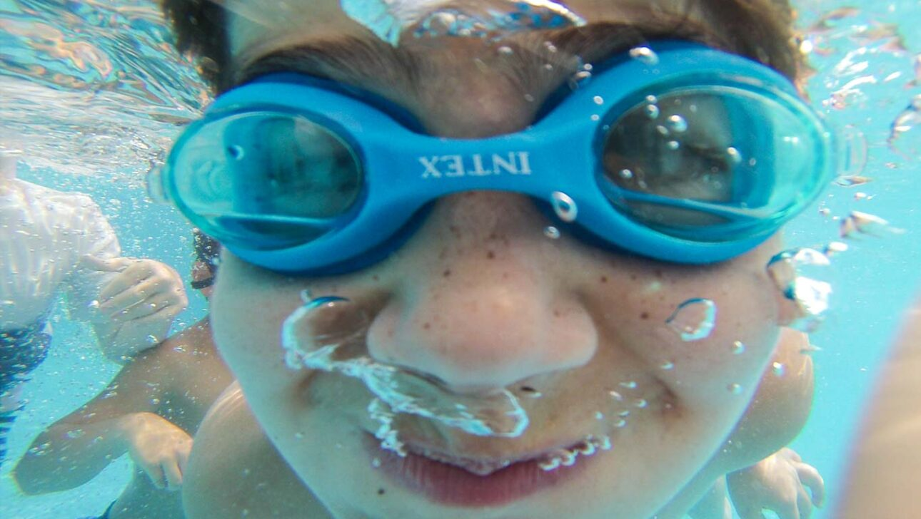 Child swimming with goggles under water.