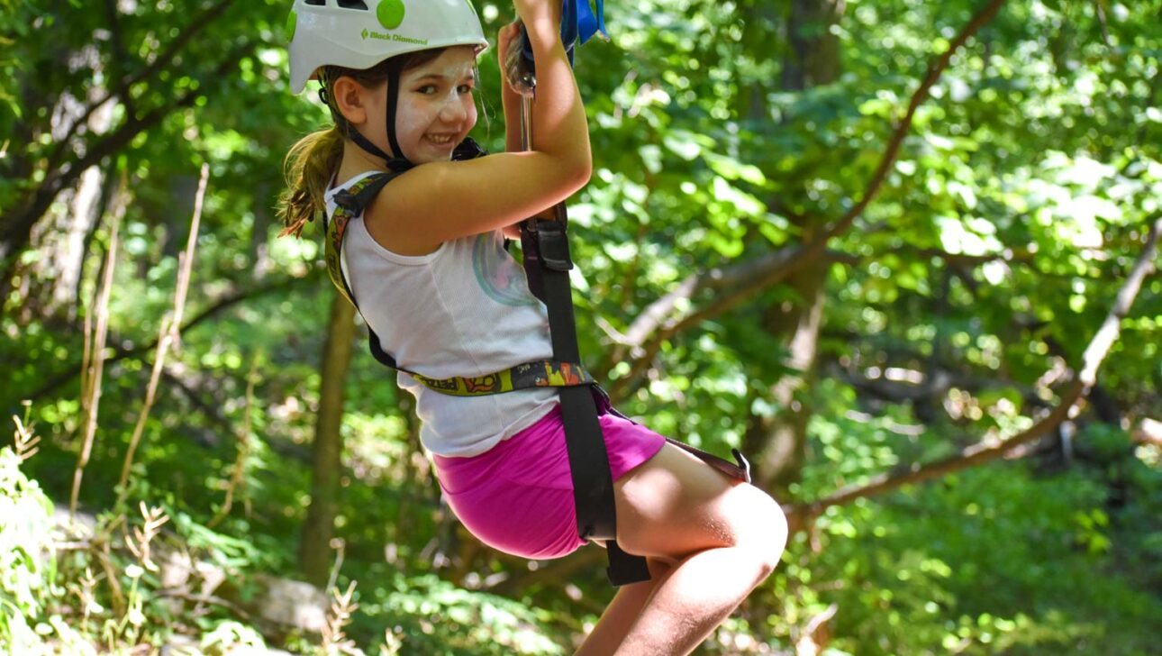 Girl zip-lining and smiling.