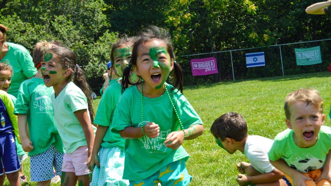 Children wearing green shirts and facepaint.