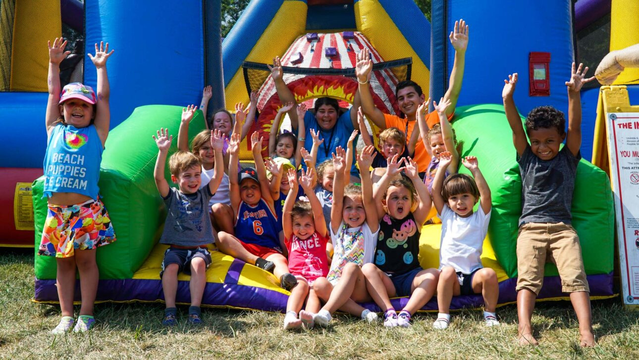 Children smiling outside a moonbounce.