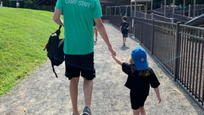 Camp staff walking with a young camper.