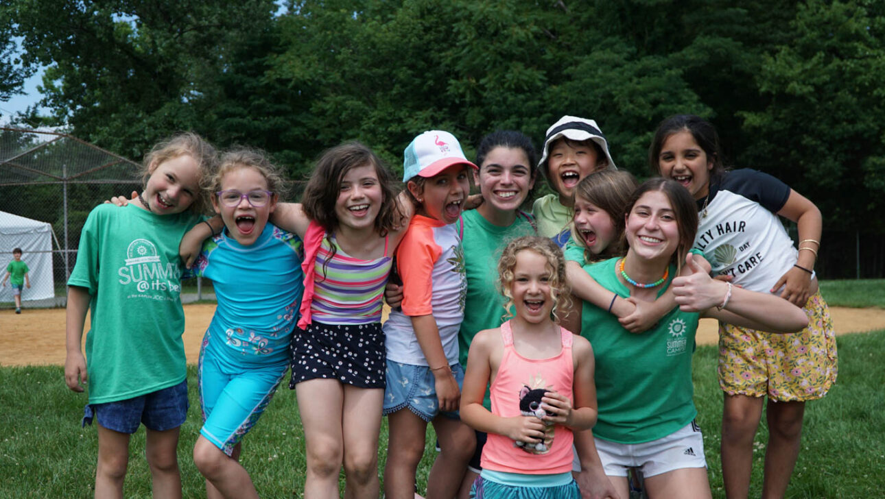 Group of girl campers smiling outside.