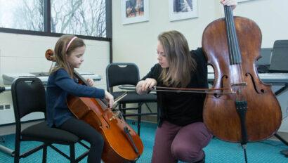 Teacher giving cello lesson to a young girl.