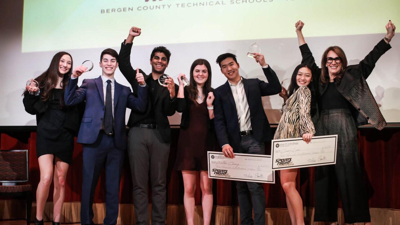 Group of students holding big checks.