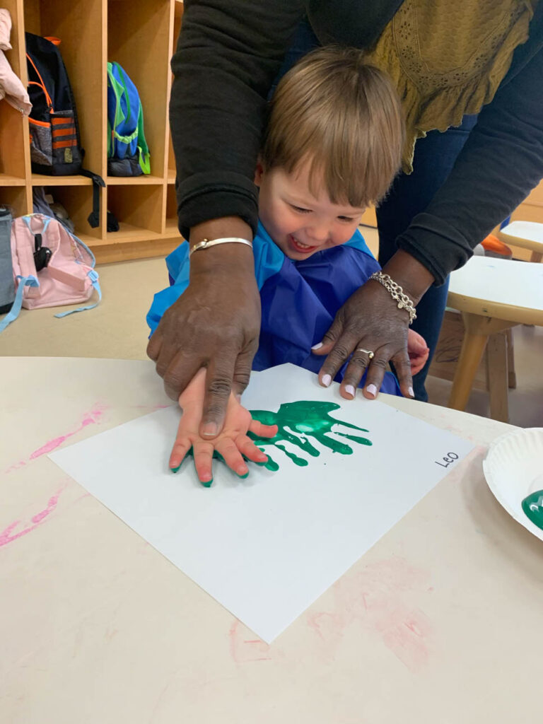Child making hand prints with paint and paper.