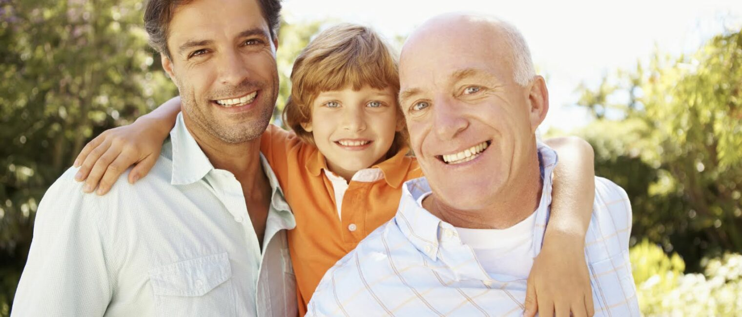 Three male generations of one family smiling together - portrait.