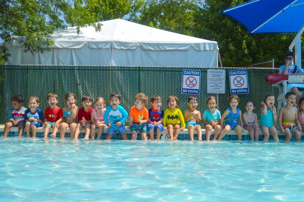 Children sitting by the pool.