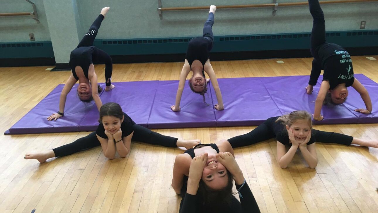 Girls stretching in a gym class.