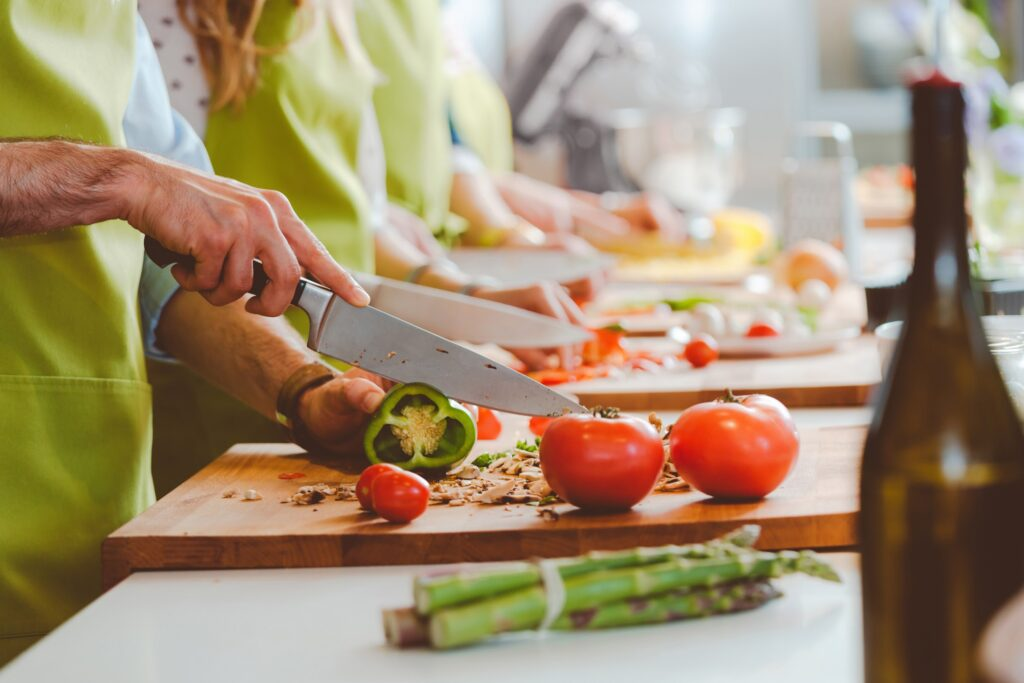 Women cooking and cutting a tomato with a knife.