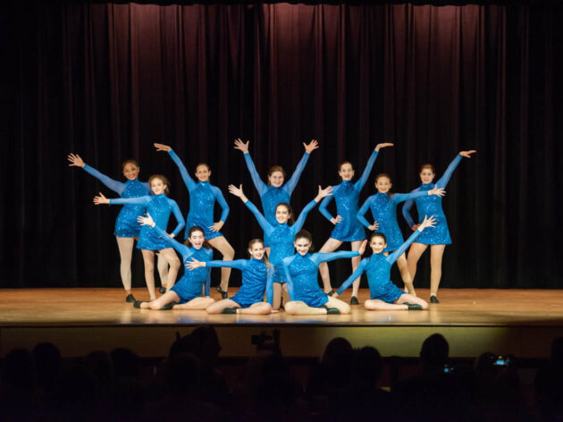 Dance performance on stage all in blue leotards.