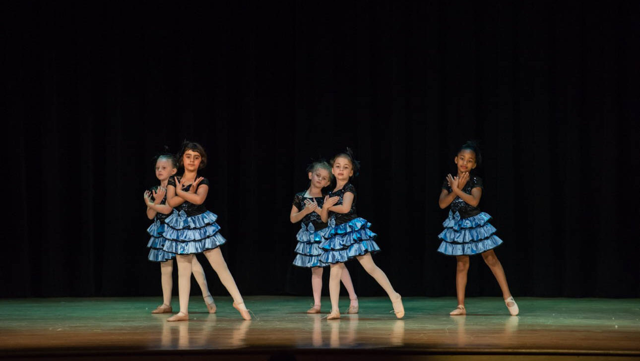 Dance performance on stage with blue skirts.