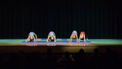 Dance performance on stage doing back bends.