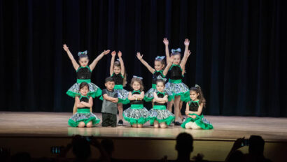 Dance performance on stage in green skirts.