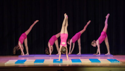 Dance performance on stage doing hand stands in pink leotards.