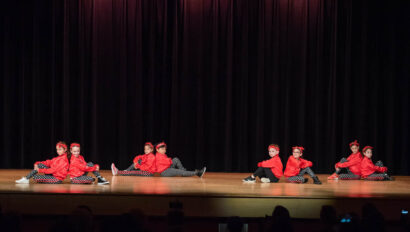 Dance performance on stage in red costumes.