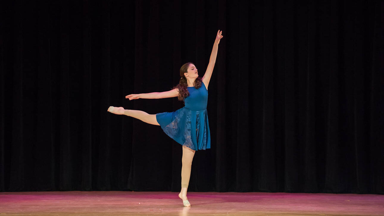 Solo ballet performance on stage.