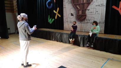 Drama teacher talking with students.