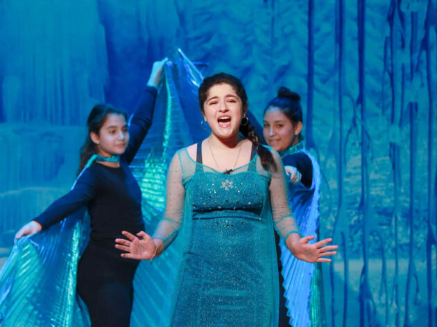 Girl playing Elsa on stage in The Frozen musical.
