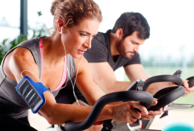 Two people on exercise bikes.
