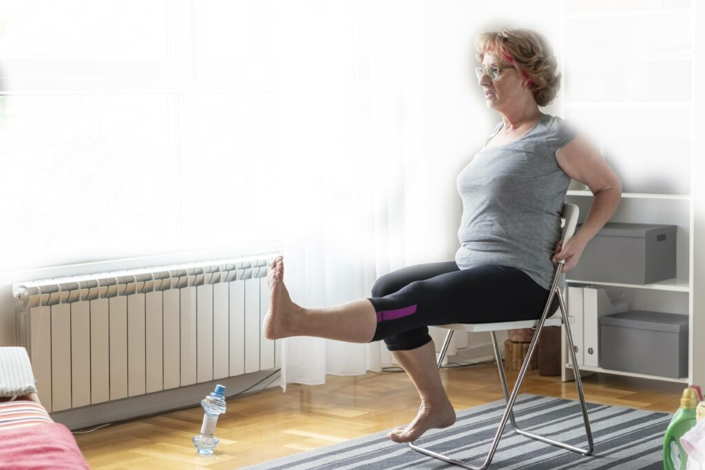 Woman excising on a chair at home.