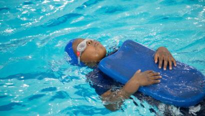 Kid swimming on his back using a kickboard.