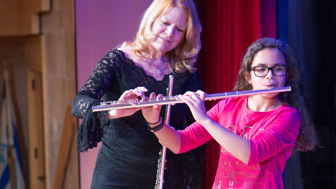 Teacher giving flute lesson to a young girl.
