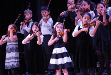 Children playing the violin on stage.